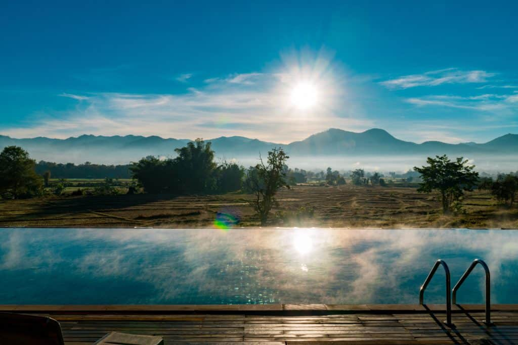 Sun rise over the mountains and a swimming pool in Pai
