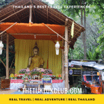 A small wooden hut with a golden Buddha and offerings inside in a forest in Chiang Mai