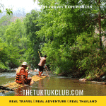 An adventurous traveller sitting on a bamboo raft floating through the forest of Northern Thailand