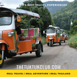 Five Tuk Tuks in convoy on a Thailand adventure driving down a small road with mountains and forest in the background