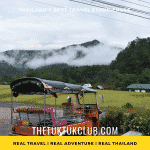 A Tuk Tuk in the foreground overlooping rice fields and mist over forest and hills in Mae Khlang Luang, Northern Thailand
