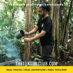 A man making fresh mountain coffee over a wooden fire in a forest in Northern Thailand
