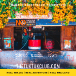 A traditional petrol station surrounded by bright orange flowers in the mountains of Northern Thailand