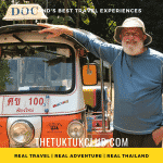 A man with a big smile standing next to his Tuk Tuk on a Thailand Adventure