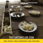 Traditional rural Thai food laid out in large bamboo containers with plates of rice ready for a delicious meal