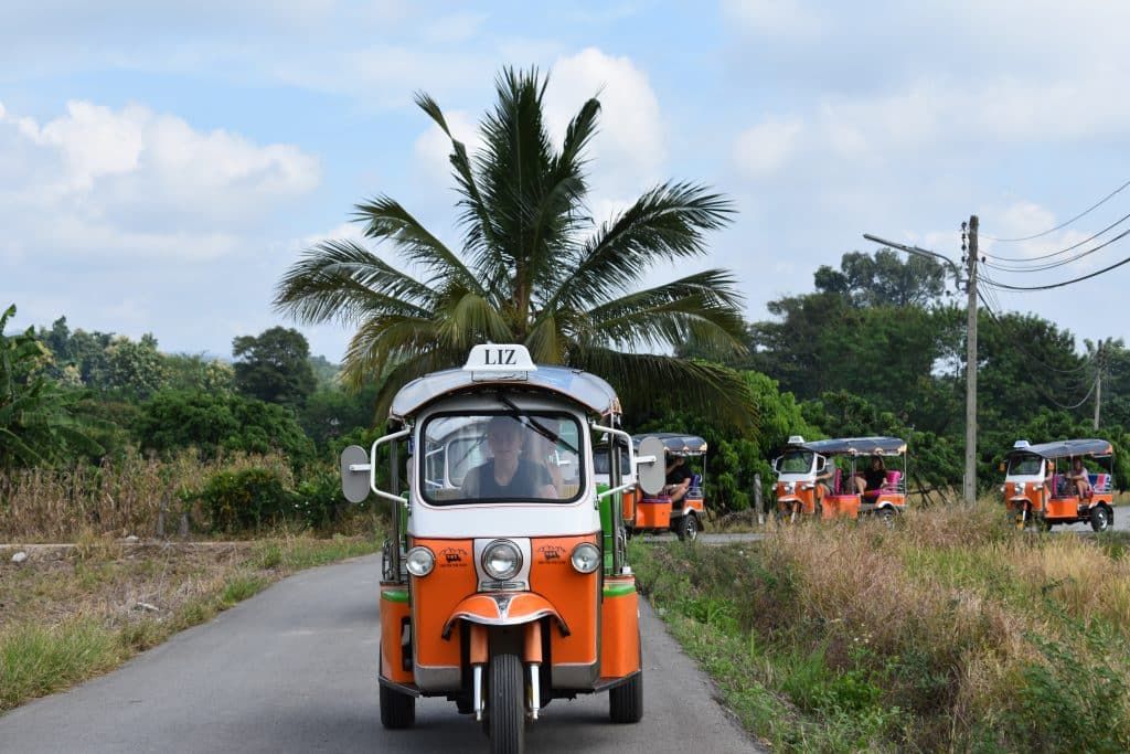 An orange Tuk Tuk on a small road with a palm tree in the background
