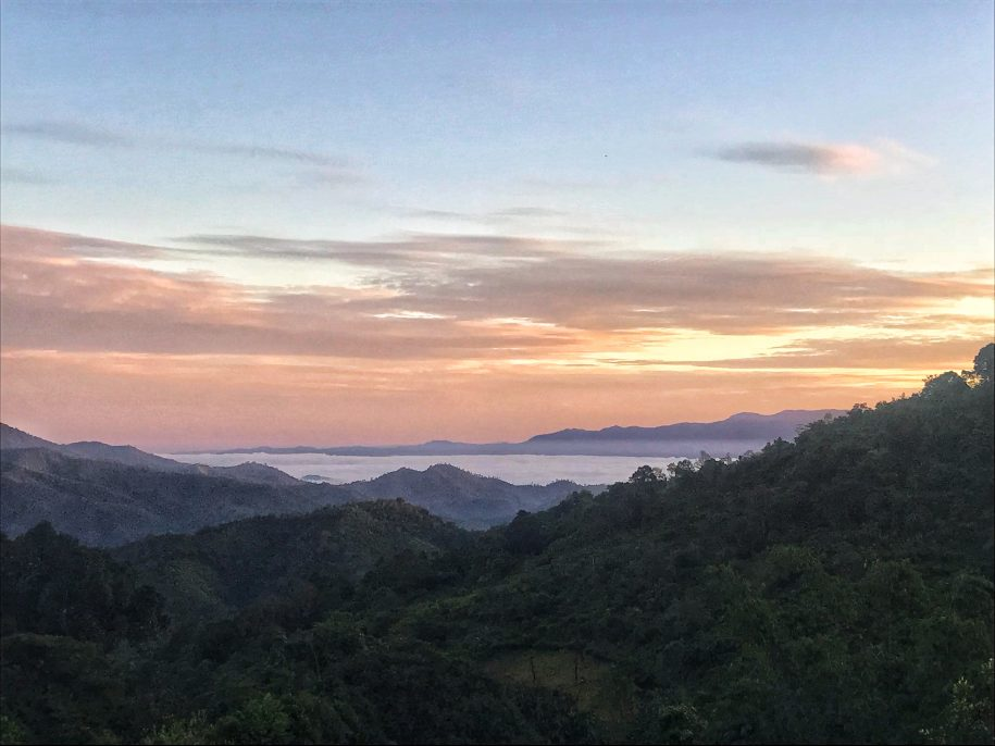 The sun setting over forested mountain in Northern Thailand with a misty valley in the distance