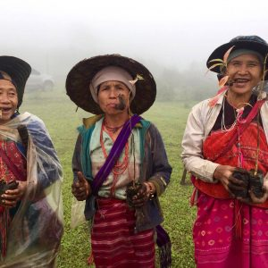 Three Karen Hill Tribe women smiling and smoking after a day working in the fields