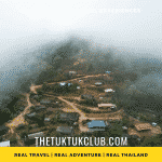 A high mountain village in the mountains on Thailand seen from above through a small gap in the clouds