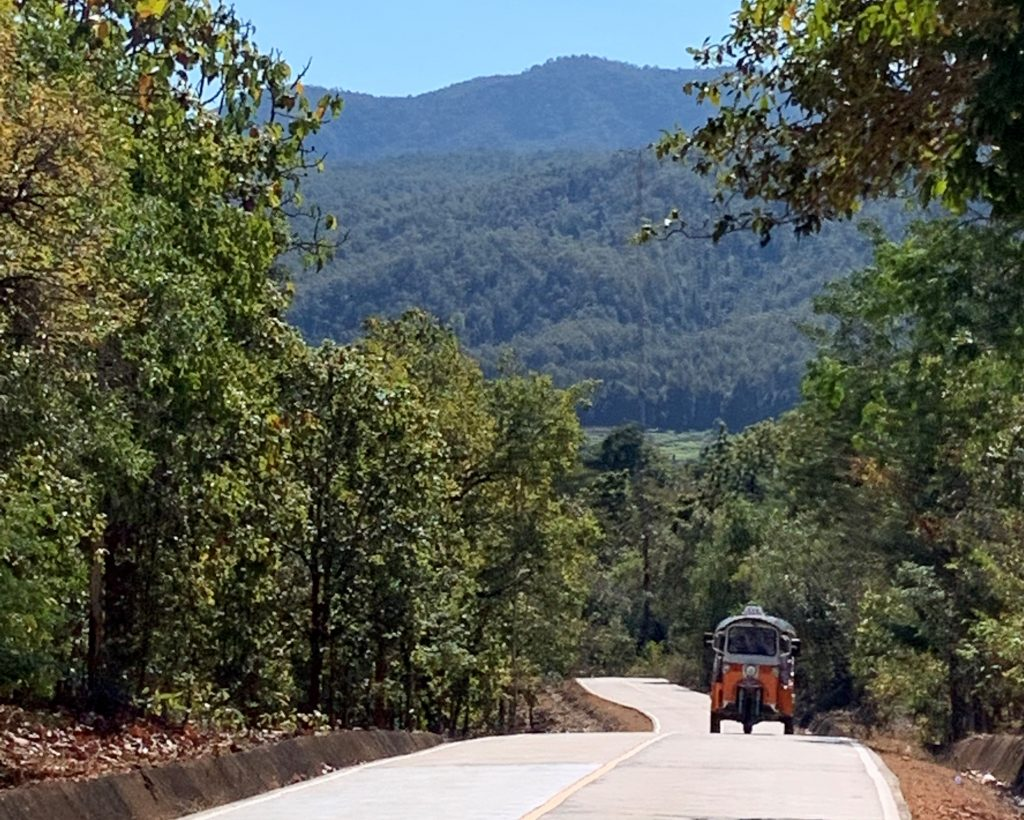 A Tuk Tuk on a winding mountain road through the mountains in Northern Thailand