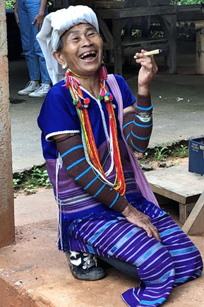 An old Karen Hill lady in traditional clothing with a big smile and smoking a countryside homemade cigarette