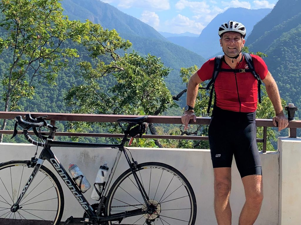 A cyclist standing next to a bike with the high mountains of Mae Hong Son in the background