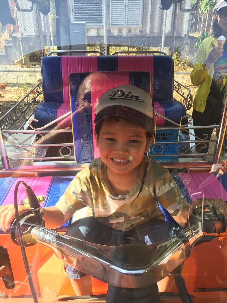 A very young boy pretending to drive a Tuk Tuk