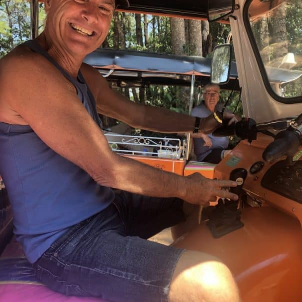 A big smile on the face of a man learning to drive a Tuk Tuk