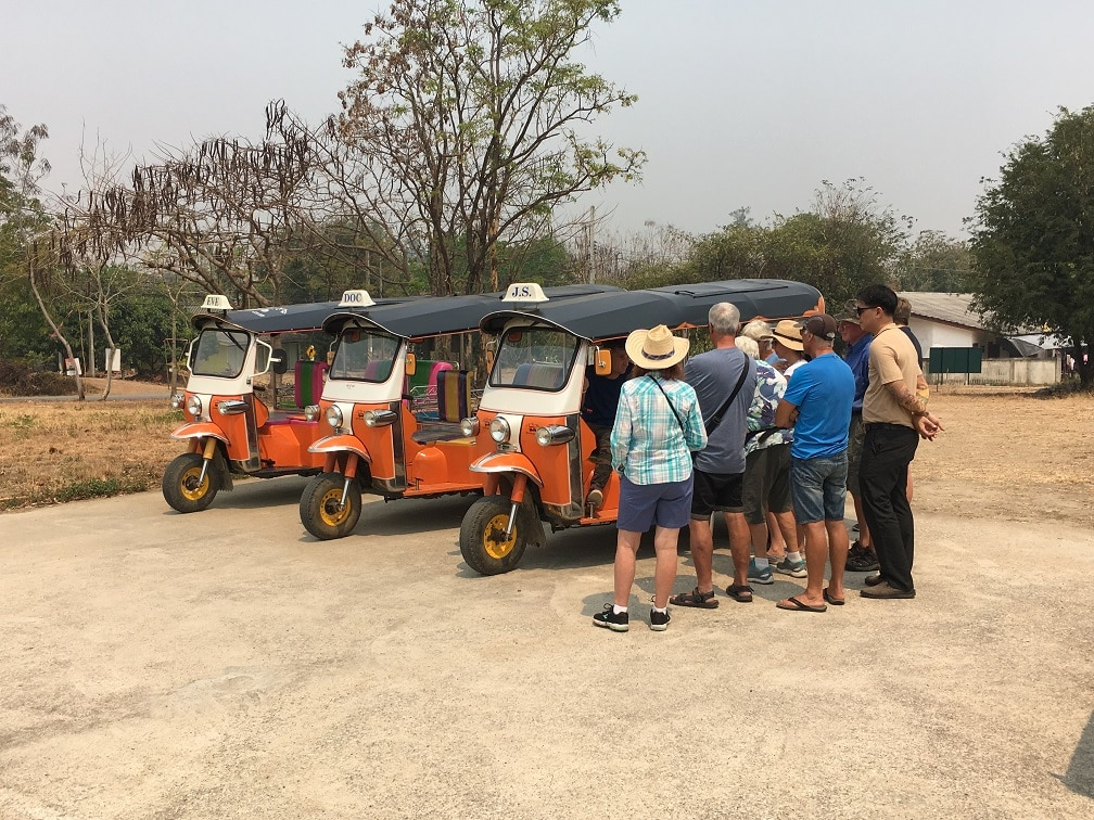 A small group of travellers learning how to drive a Tuk Tuk