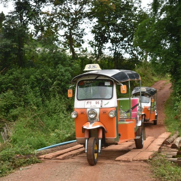 Two Tuk Tuks crossing a small wooden bridge on a dirt road