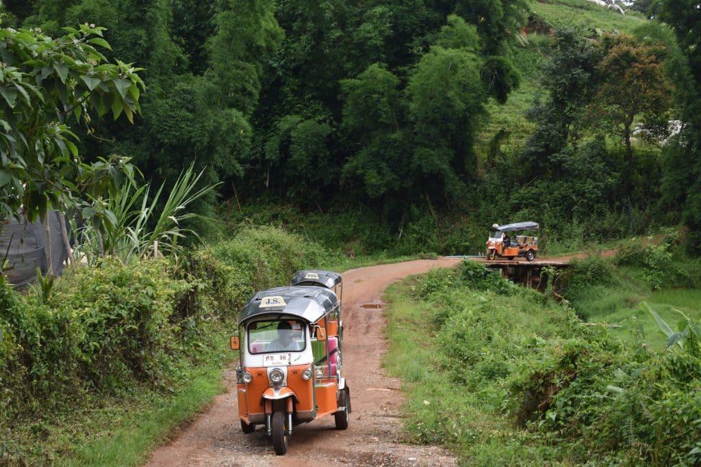 Three Tuk Tuks on a dirt road through a forest