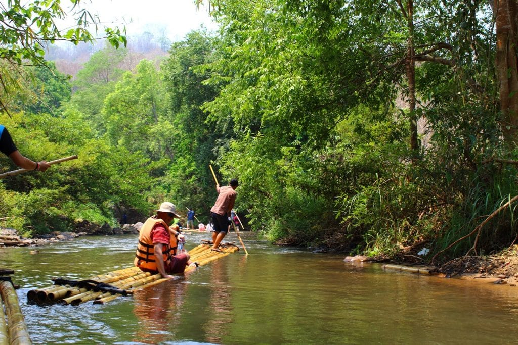 Two people floating downstream on bamboo rafts