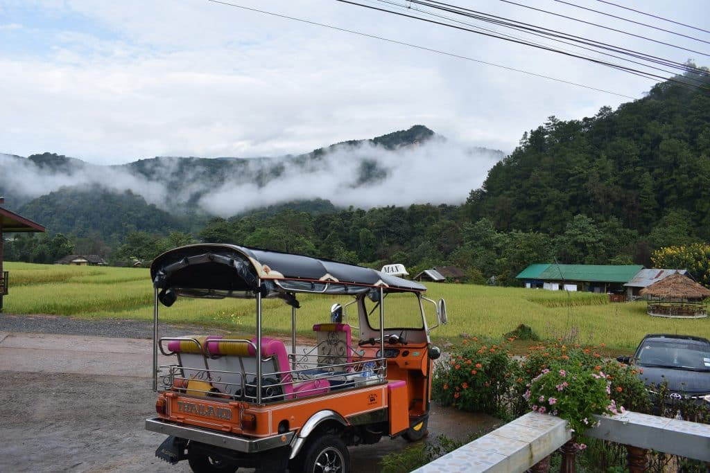 A Tuk Tuk parked in front a rice field in the mountians