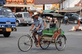 A man cycling with a traditional samlor Tuk Tuk