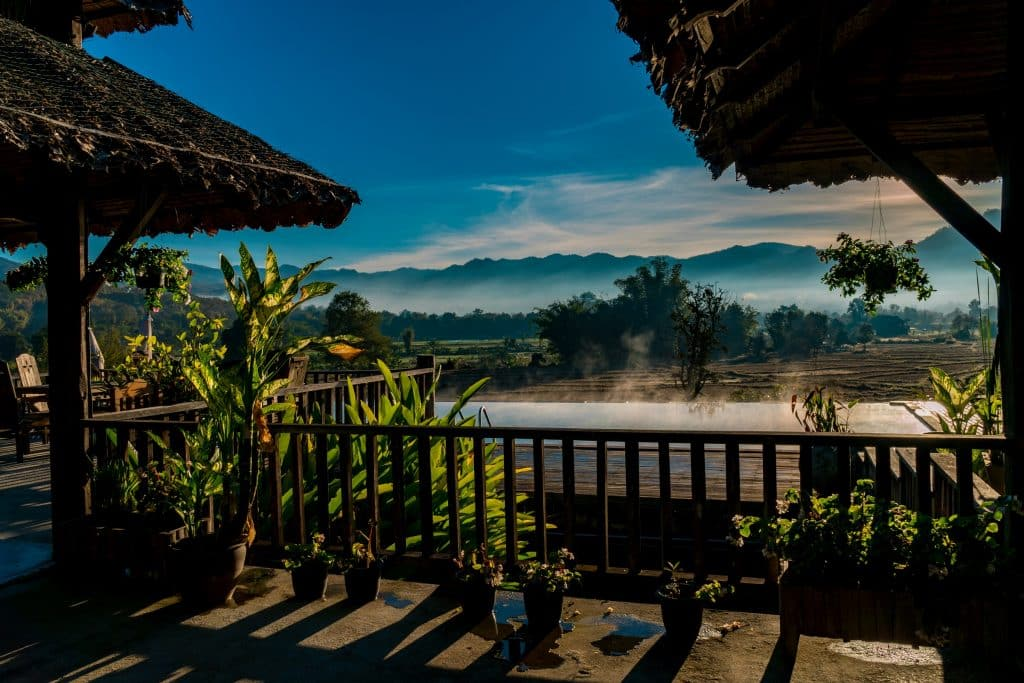 Misty mountains in the distance with a resort and infinity pool in the foreground