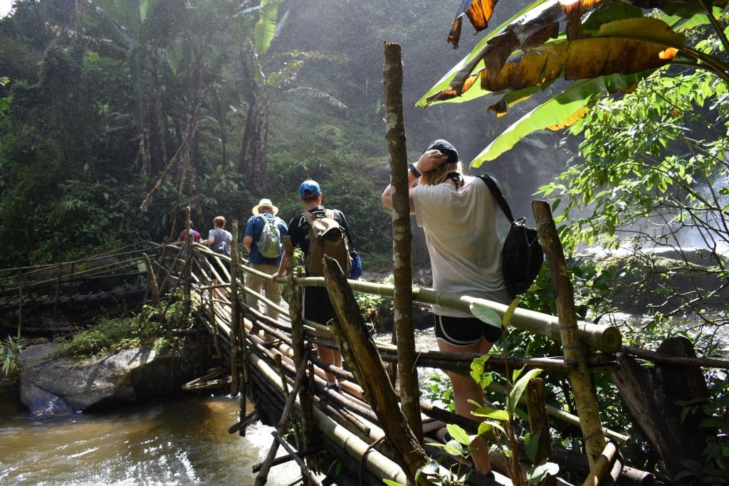 Four people crossing a wooden bridge in the jungle of Thailand