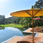 An infinity pool with sun loungers and umbrellas