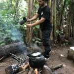 A man brewing coffee in the jungle