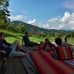 4 people relaxing on a wooden terrace in the Thai mountains
